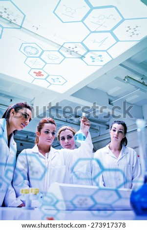 Medical interface against cute chemistry students looking at a fkask - stock photo