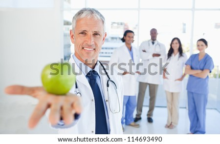 Medical interns in the background looking at their doctor who is holding an apple - stock photo