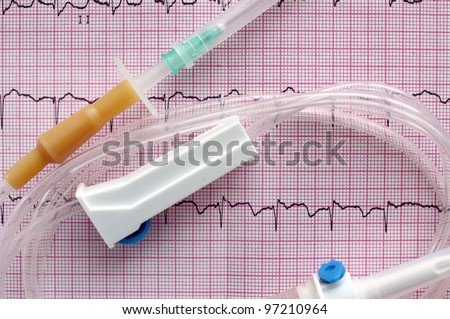 medical intravenous system on surface of electrocardiogram - stock photo