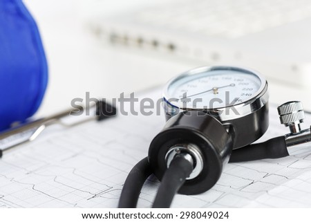 Medical manometer lying on cardiogram chart closeup. Medical help, prophylaxis, disease prevention or insurance concept. Cardiology care,health, protection and prevention. Healthy life concept - stock photo