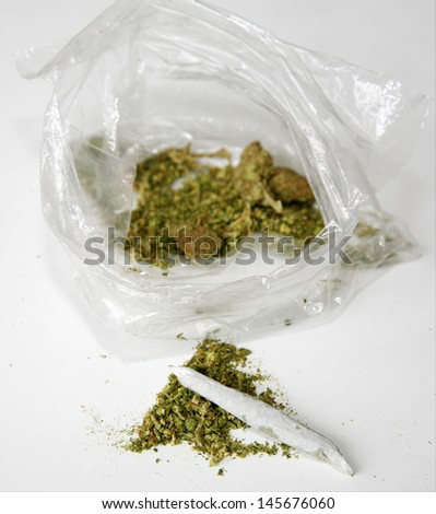Medical Marijuana aka Pot, Dope, Mary Jane, Joint, Spliff, Ganja, Weed, 420, Herb, Medicine, Hash, Hemp, Bud and many other terms. In a clear plastic sandwich bag with a Joint rolled by hand - stock photo