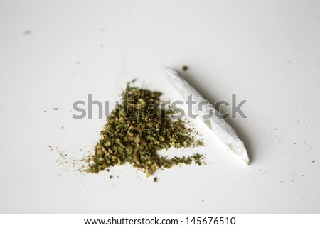 Medical Marijuana aka Pot, Dope, Mary Jane, Joint, Spliff, Ganja, Weed, 420, Herb, Medicine, Hash, Hemp and many other terms. Rolling Paper and processed pot ready to be rolled into a joint to smoke - stock photo