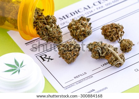Medical marijuana buds spilling out of prescription bottle with branded lid onto blank medical prescription pad on green background - stock photo