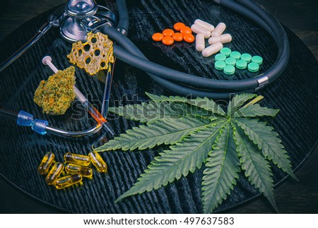 Medical marijuana products vs conventional pills, including cannabis leaf, dried bud, shatter piece, cbd caps and hash oil over black wood background