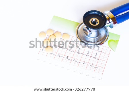 Medical, medicine stethoscope and pills with electrocardiogram on white background. Health care or illness. Tablet or drug in hospital or pharmacy. Cardiology heart treatment. Shallow depth of field - stock photo