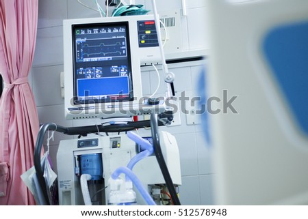 Medical monitor inside icu room, bed is foreground.