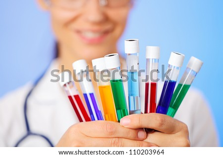 Medical multicolor test tubes with fluid sample in doctor hands closeup - stock photo