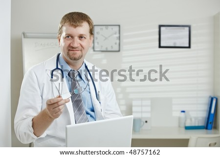Medical office - male doctor sitting, holding laptop computer in hand, explaining. - stock photo