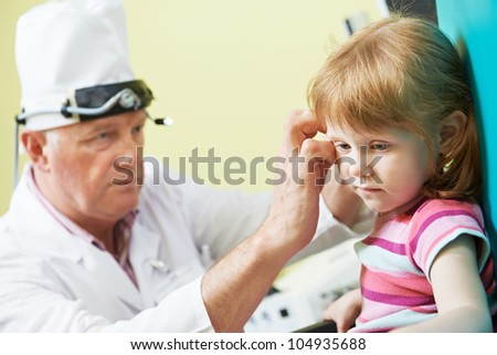 Medical otolaryngologist ear nose throat doctor examining little girl - stock photo