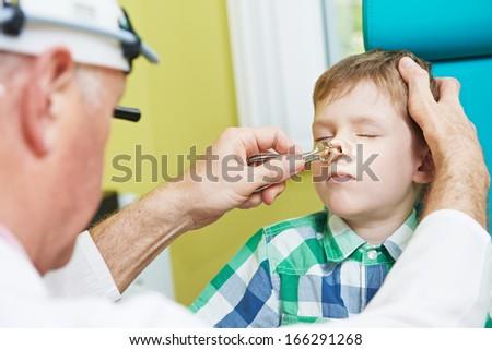 Medical otolaryngologist ear nose throat doctor rinsing nose at boy child - stock photo
