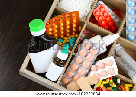 Medical pills, ampules in wooden box, on color wooden background - stock photo