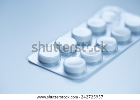 Medical pills in aluminium blister pack isolated on blue.
