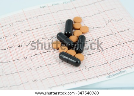 Medical pills on a ECG. Pills on a ECG strip. Hearth disease and a cure. - stock photo