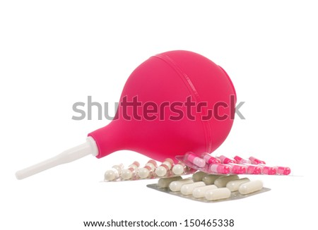 Medical pink enema and colorful pills, isolated on white background  - stock photo