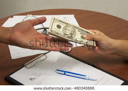 medical prescription and hand holding US dollar notes symbol for health care costs or medical insurance