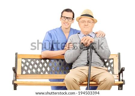 Medical professional and senior sitting on bench isolated on white background - stock photo