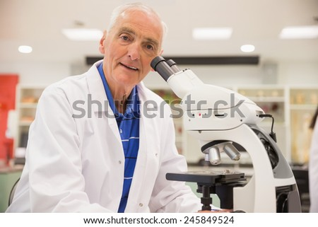 Medical professor working with microscope at the university - stock photo