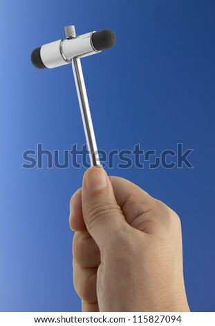 medical reflex hammer on blue background - stock photo