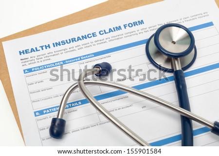 Medical reimbursement with health insurance claim form and stethoscope - stock photo