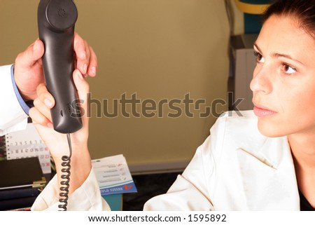 Medical secretary handing a phone to the doctor  - close up - stock photo