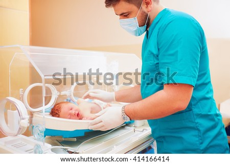 medical staff taking care of newborn baby in infant incubator - stock photo