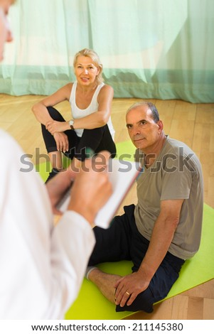 Medical staff watching yoga class for senior people indoor. Focus on man  - stock photo