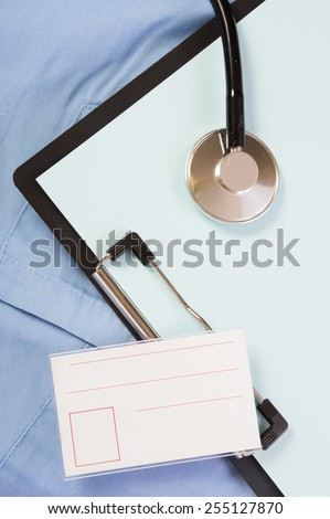Medical stethoscope and a folder with the badge on his dressing gown - stock photo