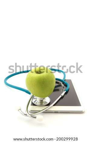 Medical stethoscope and apple on Tablet  isolated - stock photo