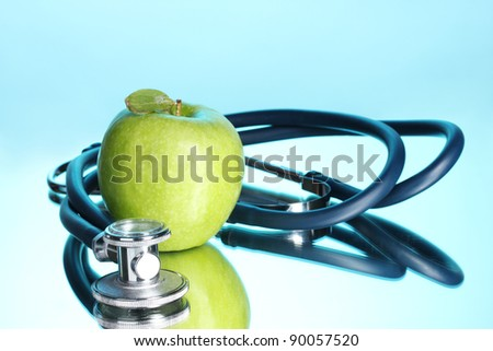 Medical stethoscope and green apple on blue