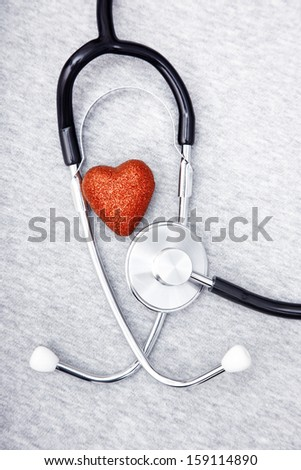 Medical stethoscope and heart on a blue textured background - stock photo