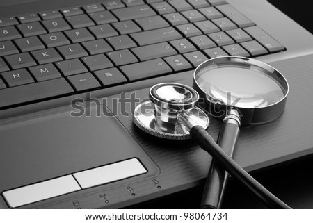 Medical stethoscope and magnifying glass on laptop keyboard. In B/W - stock photo