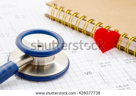 Medical stethoscope and red heart lying with diary on cardiogram chart closeup. Medical help, prophylaxis, disease prevention or insurance concept. Cardiology care,health, protection and prevention - stock photo