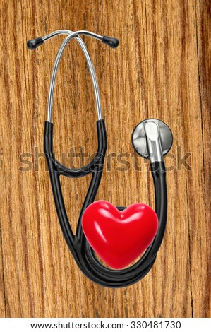 Medical stethoscope and red heart on wooden table - stock photo