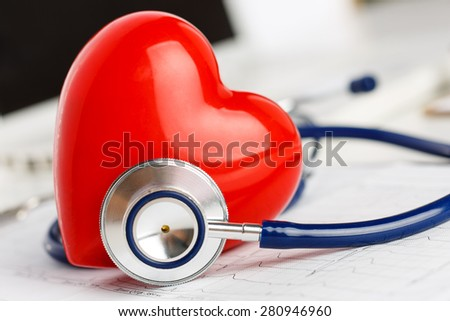 Medical stethoscope and red toy heart lying on cardiogram chart closeup. Medical help, prophylaxis, disease prevention or insurance concept. Cardiology care,health, protection and prevention - stock photo