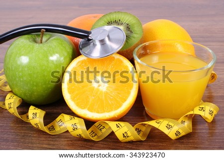 Medical stethoscope and tape measure with fresh ripe fruits and glass of juice on wooden surface plank, grapefruit orange kiwi apple, healthy lifestyles nutrition and strengthening immunity - stock photo