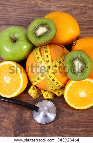 Medical stethoscope and tape measure with fresh ripe fruits on wooden surface plank, grapefruit orange kiwi apple, healthy lifestyles and nutrition - stock photo