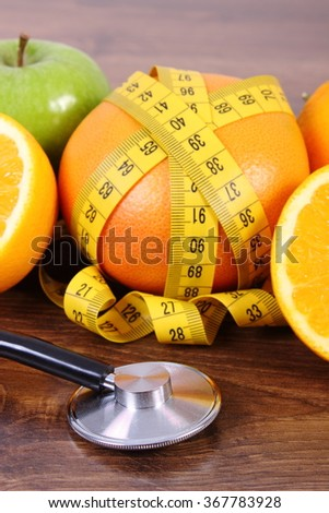 Medical stethoscope and tape measure with fresh ripe fruits on wooden surface plank, grapefruit apple, healthy lifestyles and nutrition - stock photo