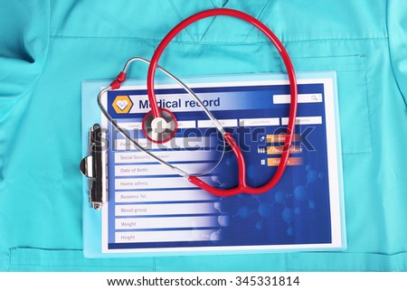 Medical stethoscope, clipboard and doctor's uniform close-up - stock photo