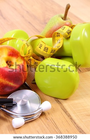 Medical stethoscope, fruits and dumbbells for using in fitness, concept of health care, healthy lifestyles and nutrition