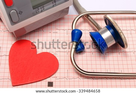 Medical stethoscope, instrument for measuring blood pressure and red heart shape on electrocardiogram graph, ekg heart rhythm, medicine concept - stock photo