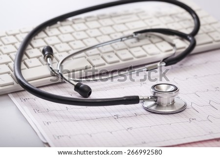 Medical. Stethoscope on cardiogram concept for heart care on the desk.blue toned images. - stock photo