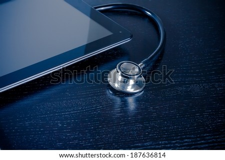 medical stethoscope on modern digital tablet pc in laboratory on wood table. Concept of medical or research theme - stock photo