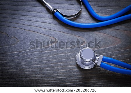 Medical stethoscope on vintage wooden board medicine concept