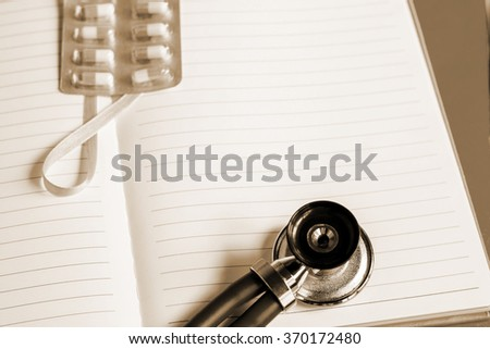 Medical stethoscope, pills on the notebook or notepad on blue background. Medicine, health hospital equipment for health care, treatment. Closeup pulse diagnostic instrument - stock photo
