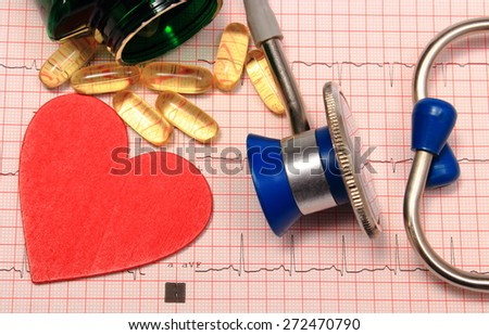 Medical stethoscope, tablets and heart shape on electrocardiogram graph, ekg heart rhythm, medicine concept - stock photo