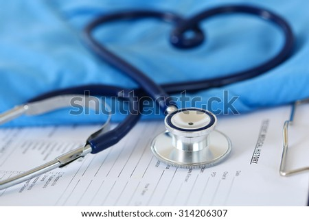 Medical stethoscope twisted in heart shape lying on patient medical history list and blue doctor uniform closeup. Medical help or insurance concept. Cardiology care, health, protection and prevention