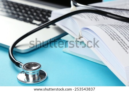 Medical stethoscope with books and laptop on blue background
