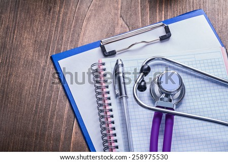 medical stethoscope with purple tubes on clipboard with ballpoint pen and vintage wooden board horizontal version medical comcept   - stock photo