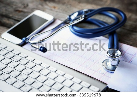 Medical still life with keyboard on wooden table - stock photo