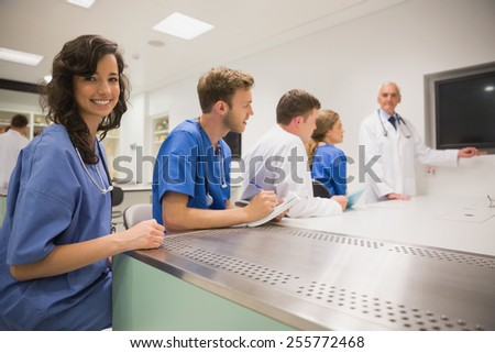 Medical student smiling at the camera during class at the university - stock photo
